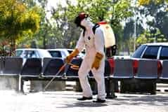 A worker wearing protective gear disinfects an area as a precaution against the ... 1