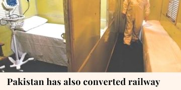 In the photo: A man in protective suit walks in a railway coach at Rawalpindi st... 1