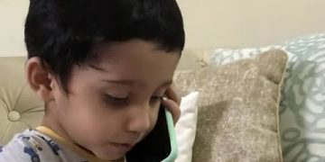 Sweet toddler speaks baby talk while pretending to have phone conversation