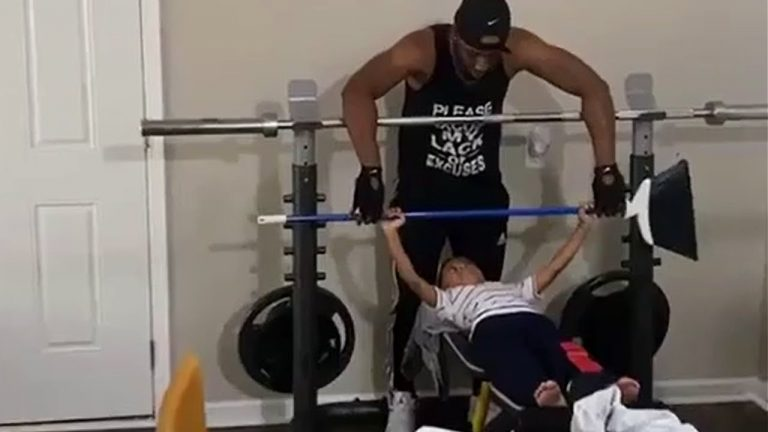Little boy learns how to bench press at the gym
