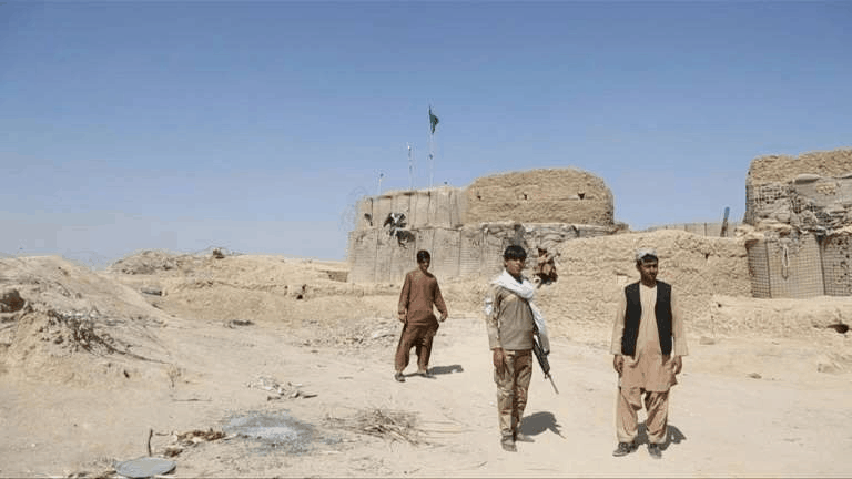 a group of people walking down a dirt road: The dry and dusty village of Aziz Abad sits on the frontline of Afghanistan's war and is currently under government control -- but only just.