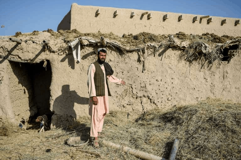 a man standing in front of a brick building: Farmer Atta Jan, 28, shows a wall hit by bullets at his house in Kandahar province