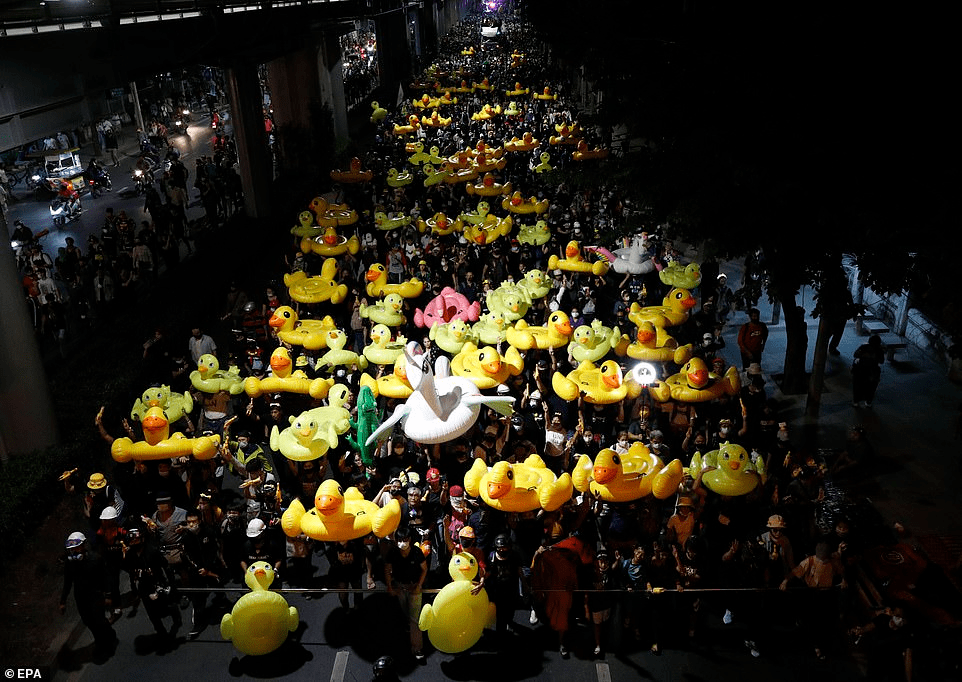 Anti-government protesters march with inflatable rubber ducks during a street protest calling for a political and monarchy reform at the 11th Infantry Regiment, the headquarters of the King's Guard regiment in Bangkok, Thailand, on Sunday night