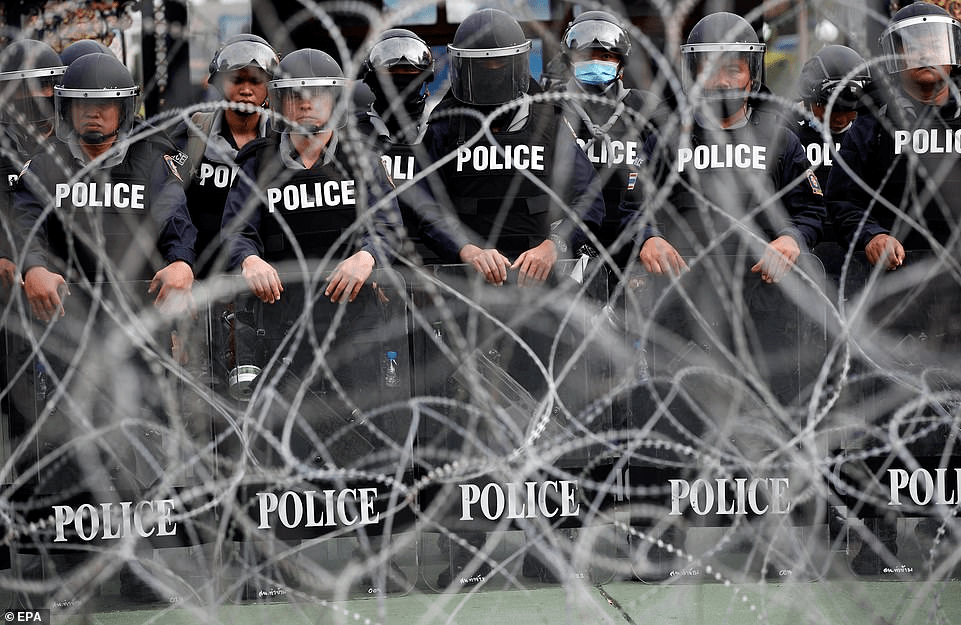 Anti-riot police officers are deployed behind barbwires during an anti-government street protest calling for a political and monarchy reform at the 11th Infantry Regiment, the headquarters of the King's Guard regiment in Bangkok, Thailand, 29 November 2020
