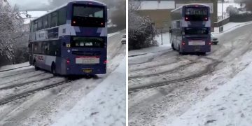 Double decker bus skids in the snow right at another car